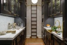 an elegant dark kitchen with traditional dark cabinets, a ladder to get things from upper cabinets and neutral stone countertops