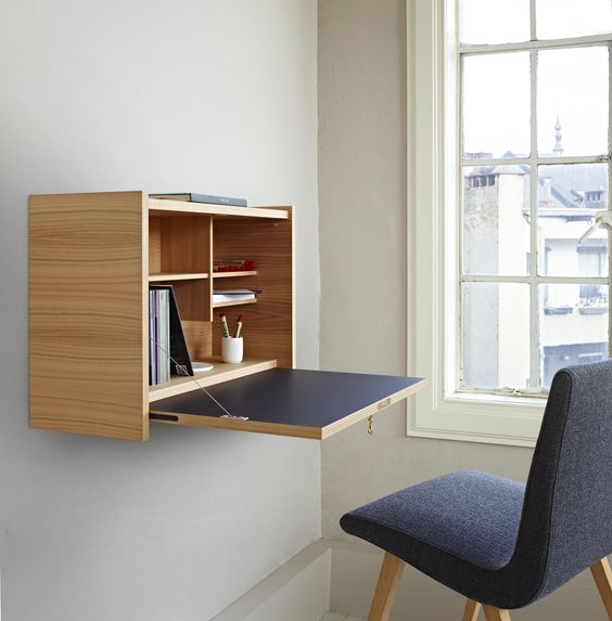 an elegant minimalist Murphy desk done in light colored plywood and navy, with stylish and neat storage compartments inside