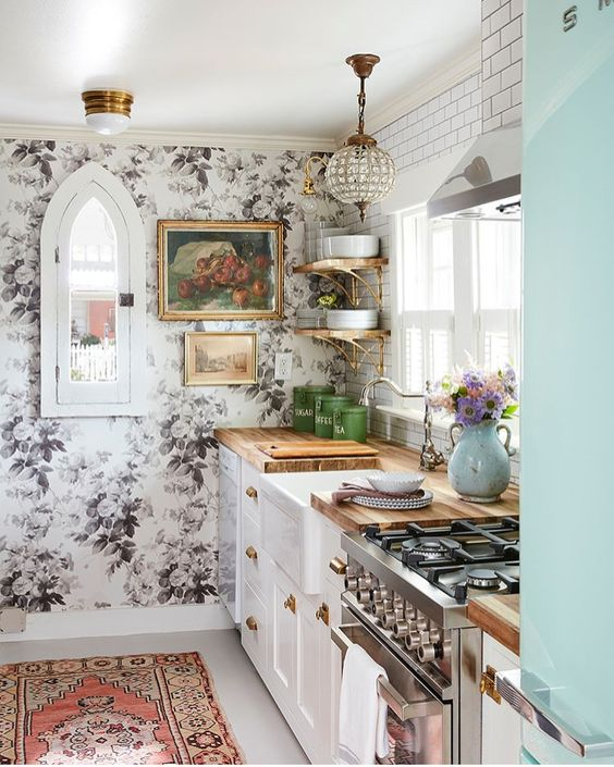 traditional white cabinets with butcherblock countertops are combined with a floral wall, a glam lamp and a boho rug
