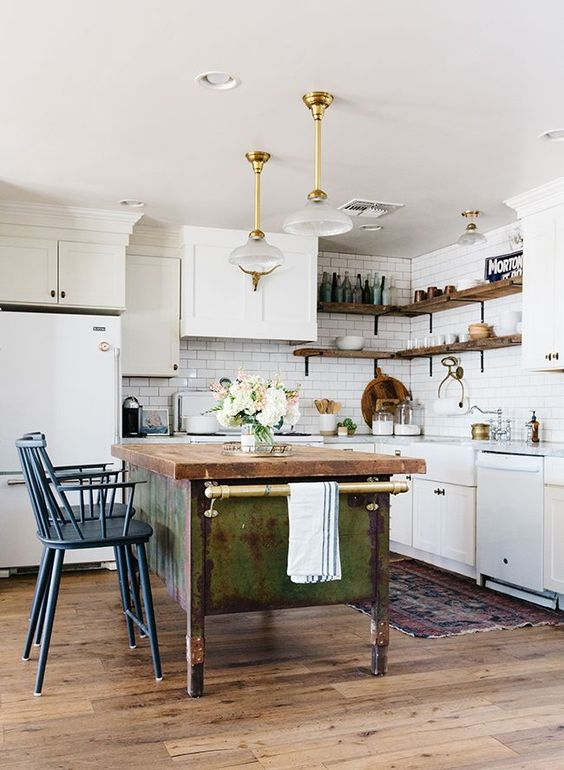 white cabinets paired with a shabby chic wooden kitchen island and vintage blue stools plus refined pendant lamps