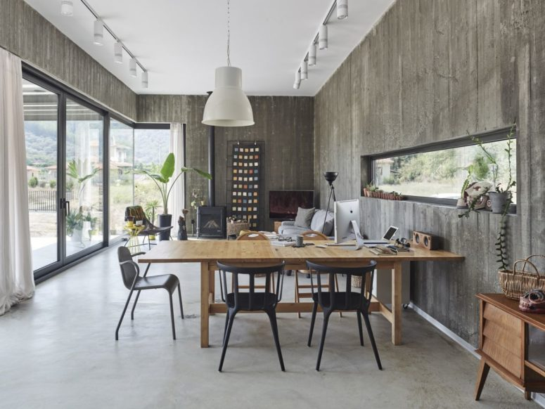 The dining or working space is done with black chairs and a wooden table