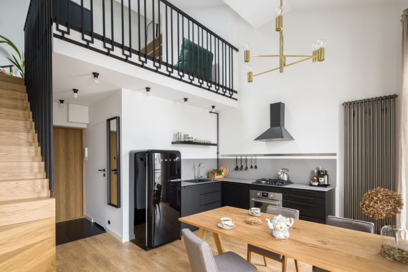 The kitchen is done in black and grpahite grey, with white countertops and a black Smeg fridge