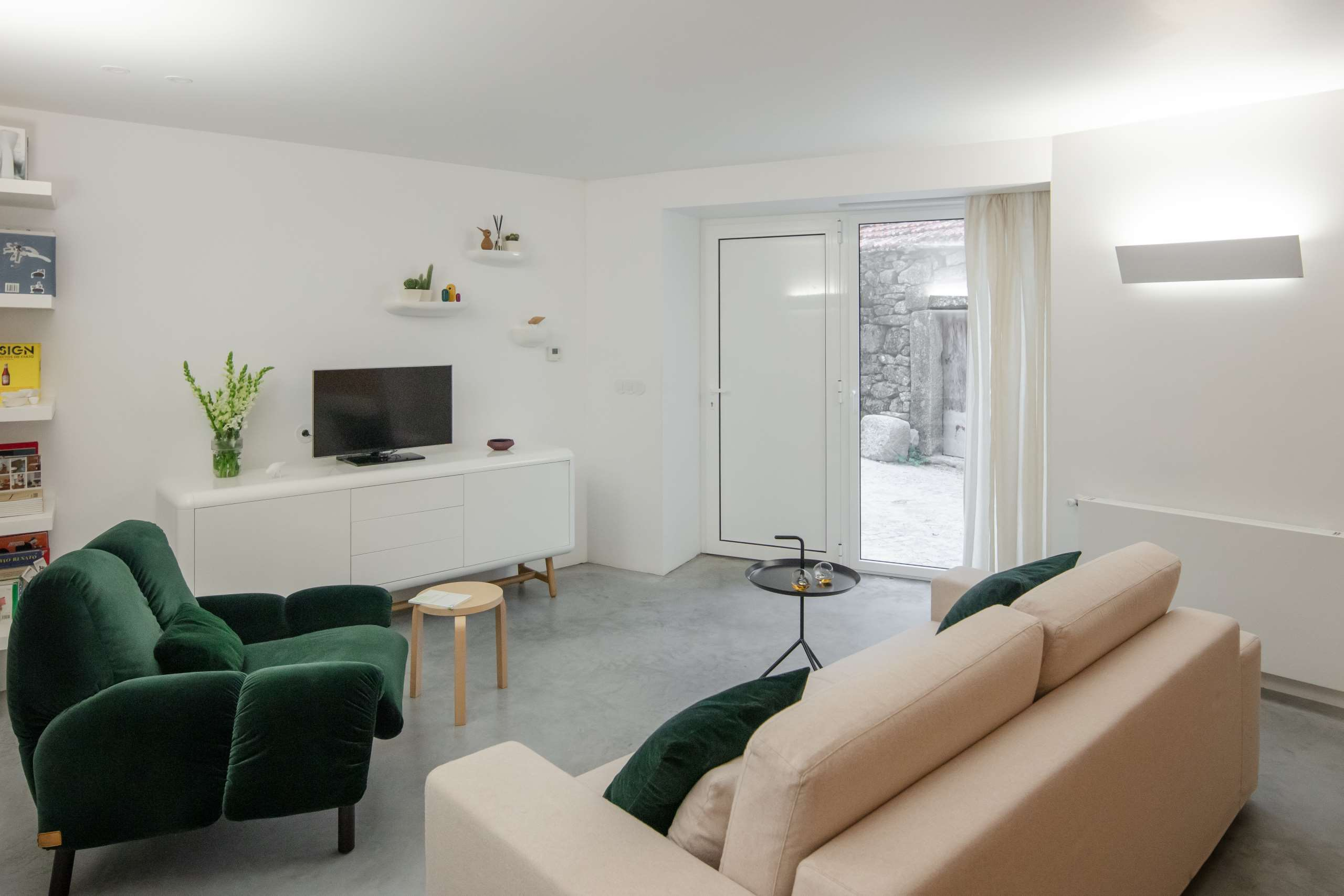 The living room features a neutral color scheme, emerald touches and some chic lights