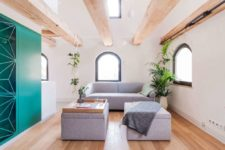 The living room is done with grey upholstered furniture, greenery and wooden beams on the ceiling