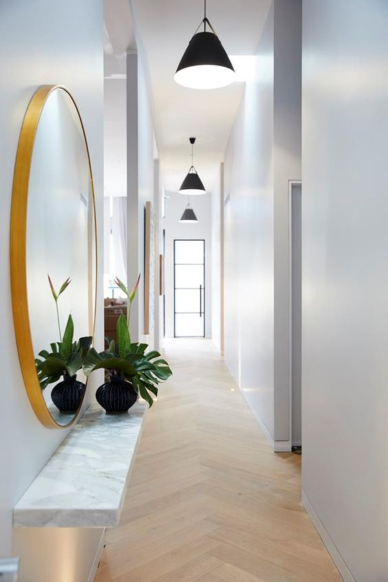 a long white Scandinavian hallway with black pendant lamps hanging in a row feels airy and lit up
