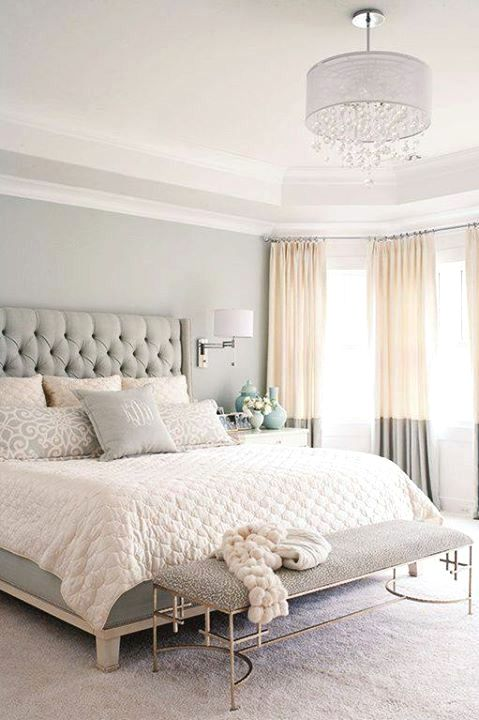 a soothing bedroom in light greys, with an upholstered bed, two tone curtains and an elegant bench