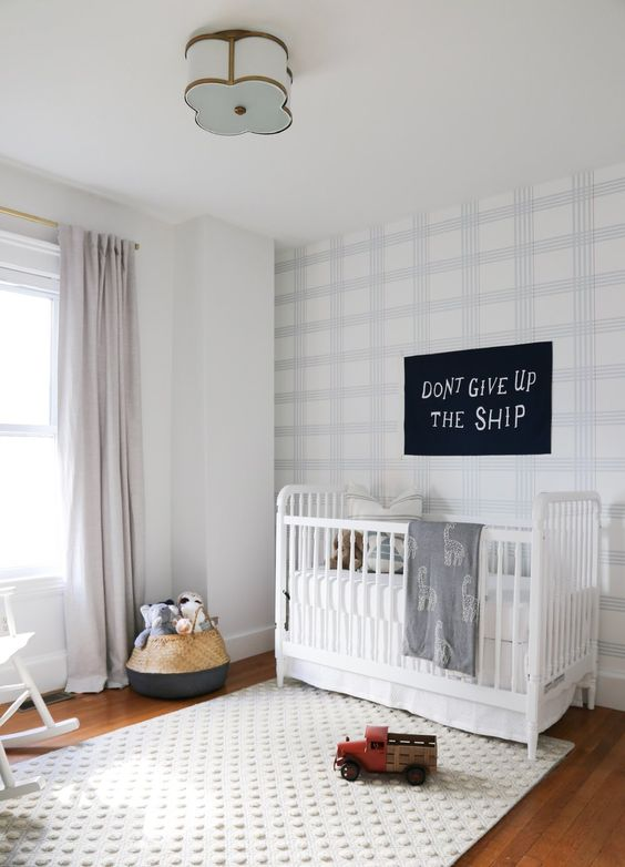 a welcoming and light filled nursery with a light shaded plaid statement wall and a fun white polka dot rug