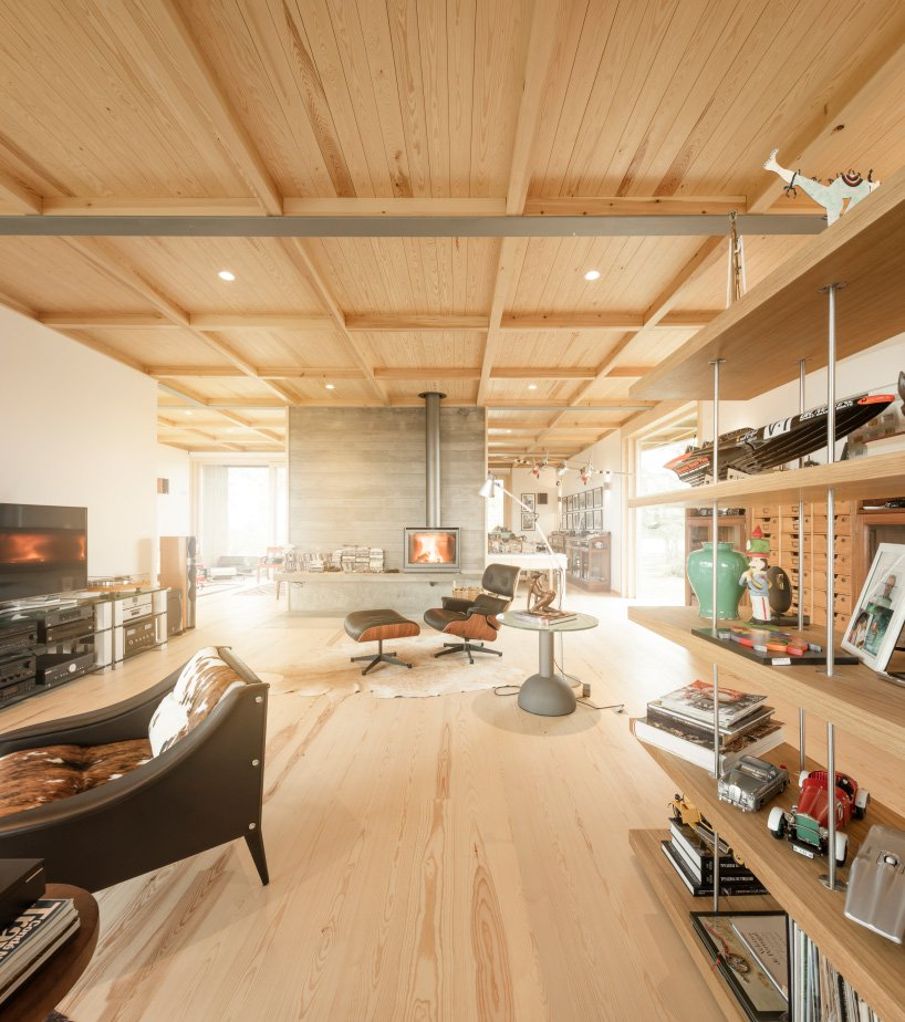 The house itself is filled with light, done with light colored wood, there's a stylish fireplace and chic furniture and it was extended with two wings
