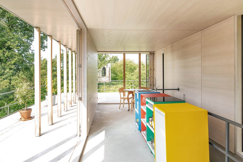 The kitchen is done with light colored plywood and a row of colorful cabinets that feature storage