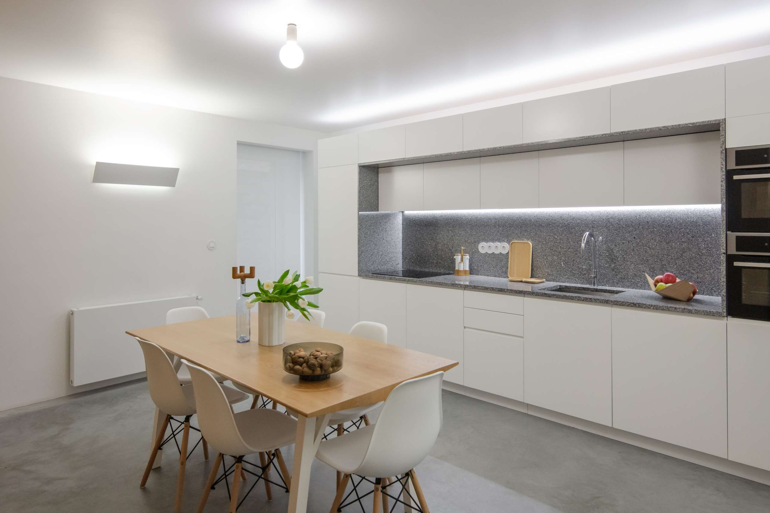 The kitchen is minimal, with a stylish dining set, sleek white cabinets and built in lights