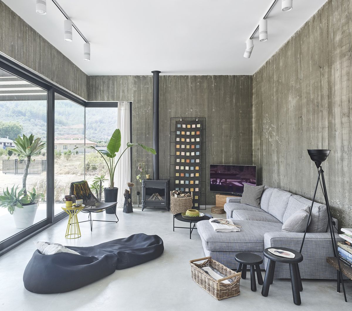 The living room is done with a hearth, a sectional sofa, bean bag chairs, a potted plant and a glazed wall for much light and views