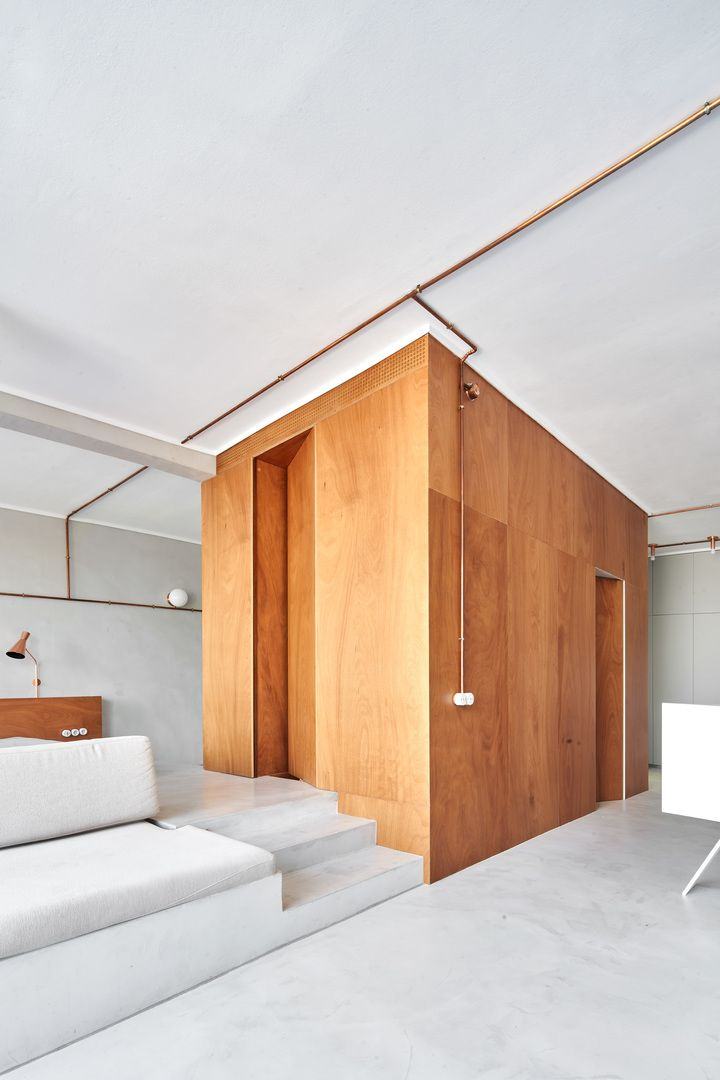 The plywood unit contains toilets, closets and laundry and divides the spaces