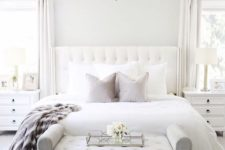 03 a chic bedroom in neutrals, with white walls, a white upholstered bed and a grey upholstered bench