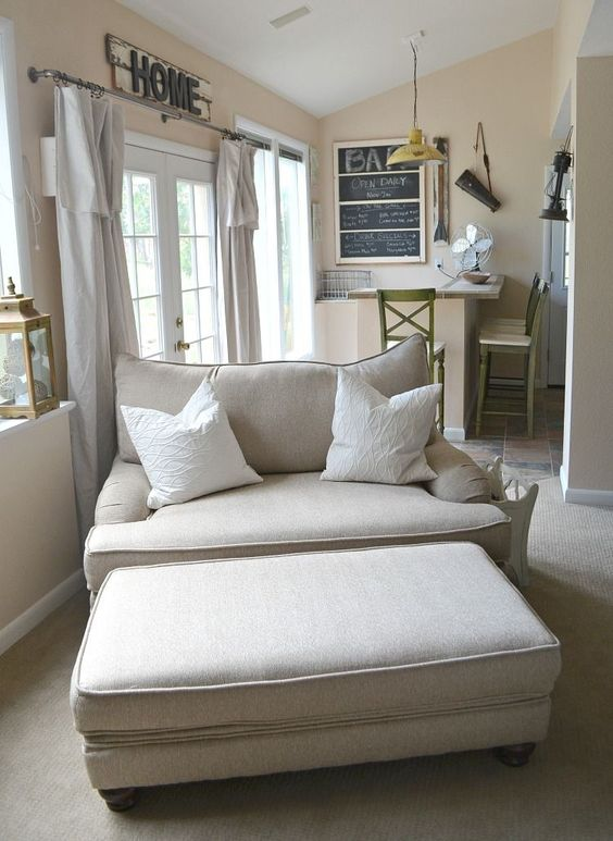 a cozy neutral loveseat and a matching ottoman perfectly fit a modern farmhouse living room