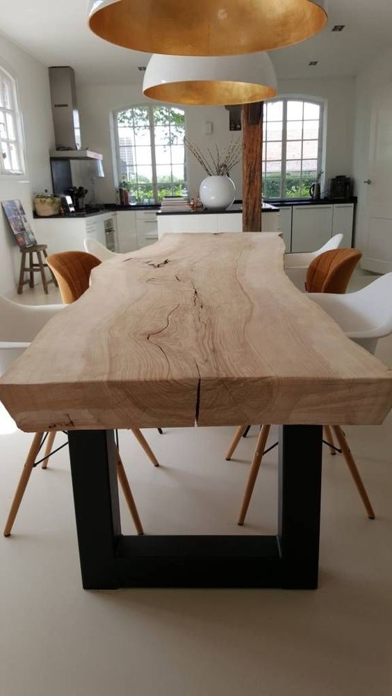a light-stained dining table of a single slab with a live edge and mismatching rust and white chairs