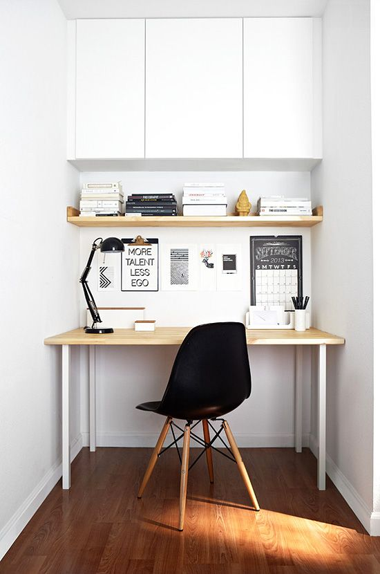a mini home office nook in white, with a closed storage space and a sleek desk plus a black lamp and chair