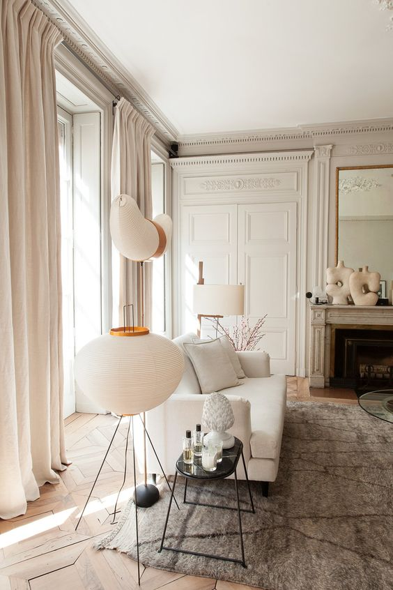 an elegant neutral Parisian living room with off-whites, greys and some beige touches is filled with light