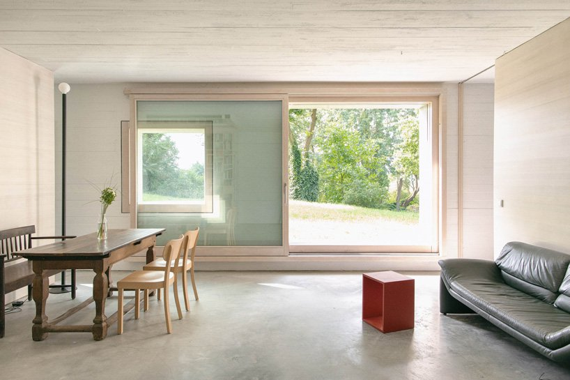 The dining space seamlessly flows into a living room, with just some furniture and glazed walls