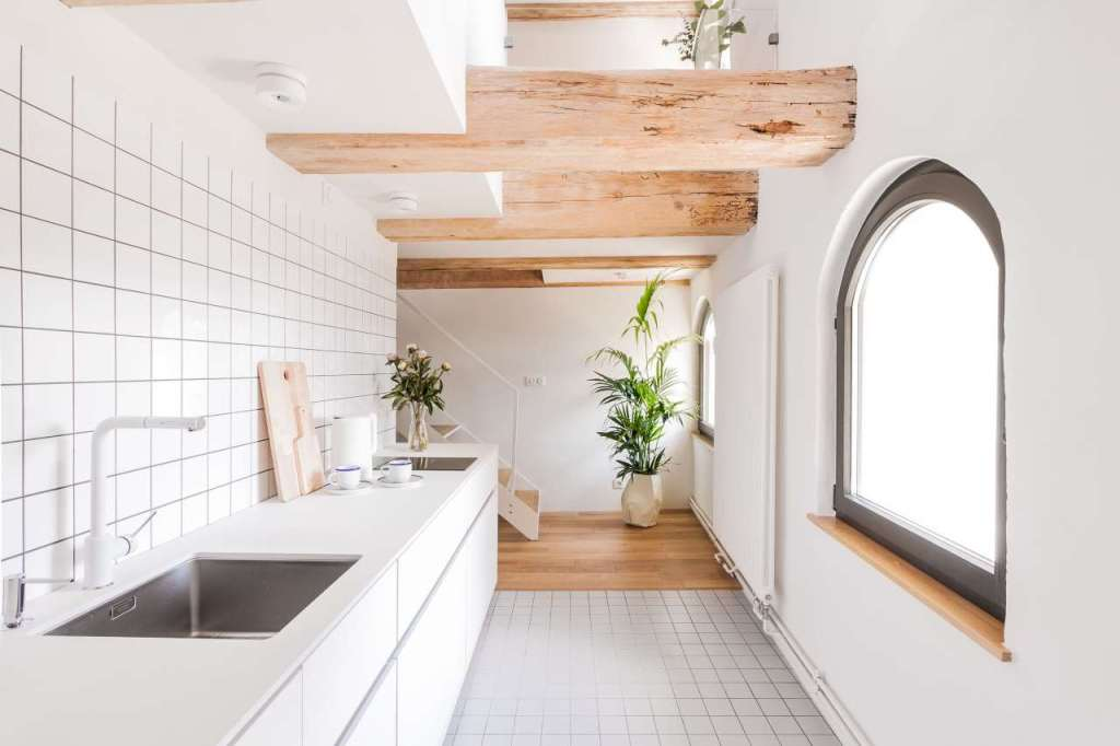 The kitchen is done in white, with simple tiles and sleek white cabinets plus matte countertops