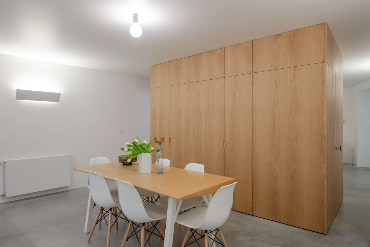 The spaces are divided with a large storage unit of light colroed plywood