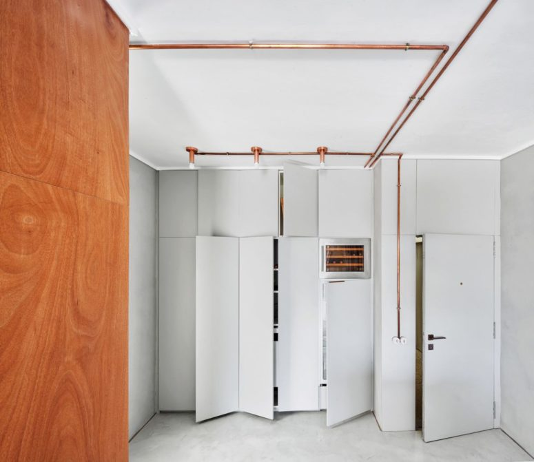 The storage is done sleek, with off-white panels and elegant piping with bulbs