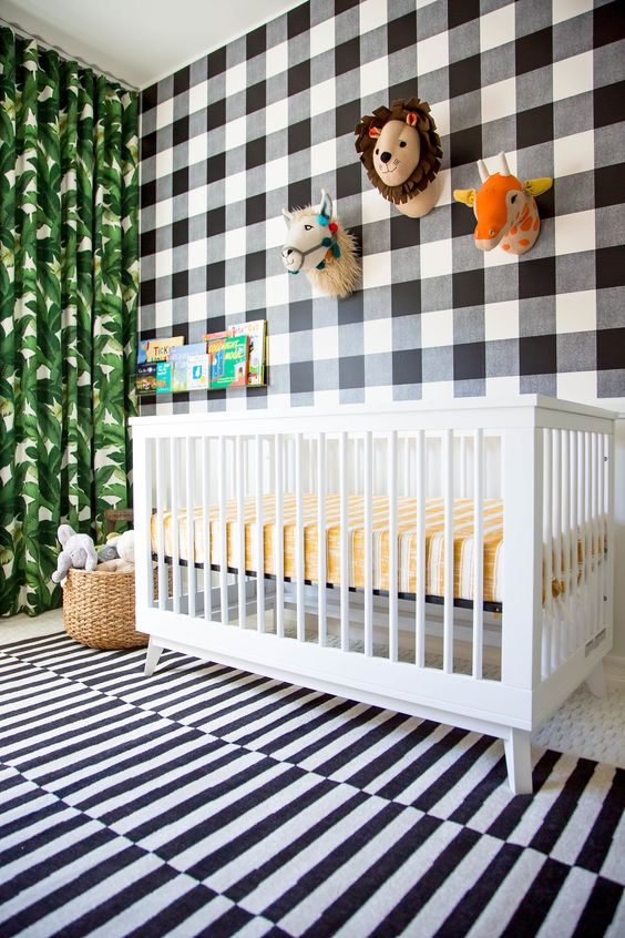 a fun tropical nursery with a mix of prints   a plaid statement wall, a striped rug and a tropical leaf print curtain