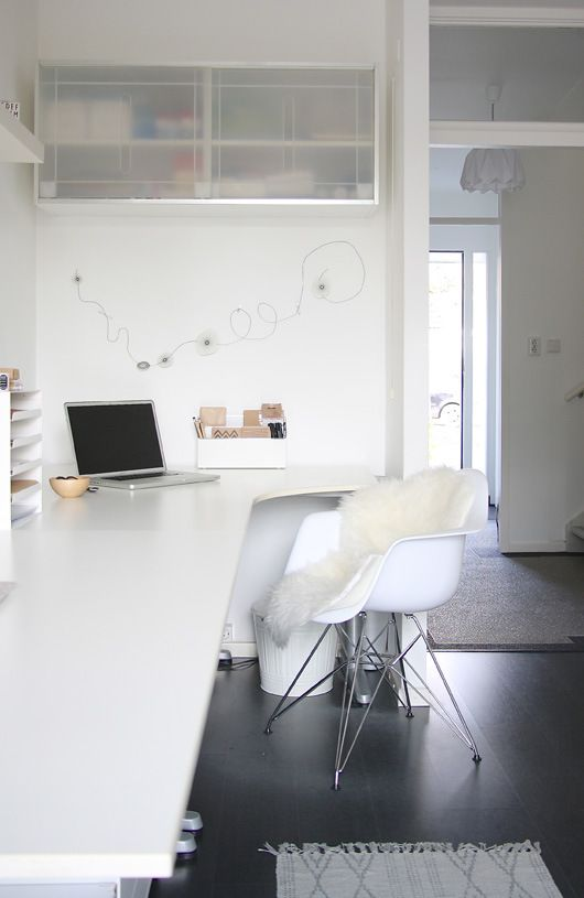 a minimalist white home office with a long and sleek desk, some wall-mounted cabinets and a comfy chair