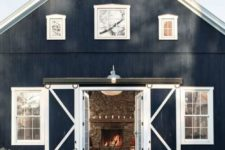 04 a navy and white barndominium with sliding doors and white framed windows looks very welcoming