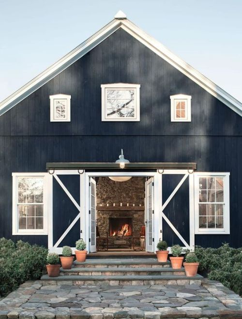 a navy and white barndominium with sliding doors and white framed windows looks very welcoming