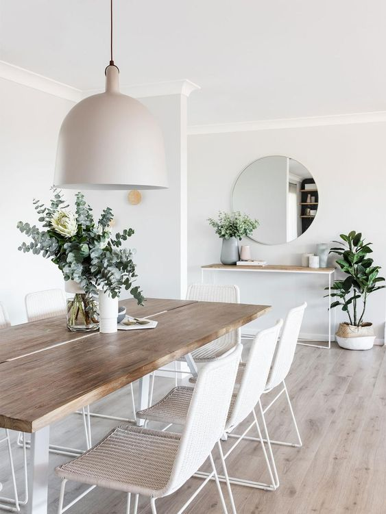 a neutral wooden dining table on white hairpin legs and matching white wicker chairs for an airy feeling