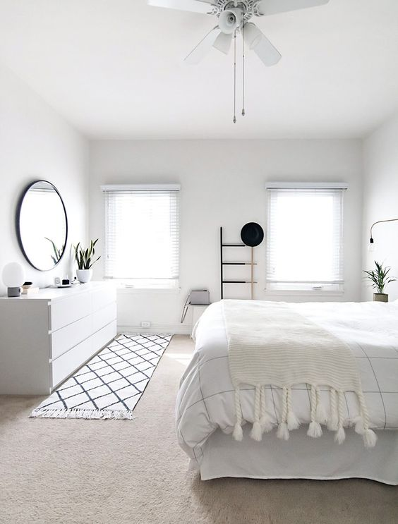a pure white bedroom with a Nordic feel, a whiet sleek sideboard and shades on the windows