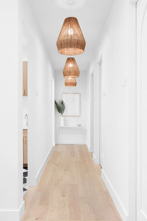 a white long and narrow hallway is done with wicker pendant lamps and tropical leaves to highlight the ambience