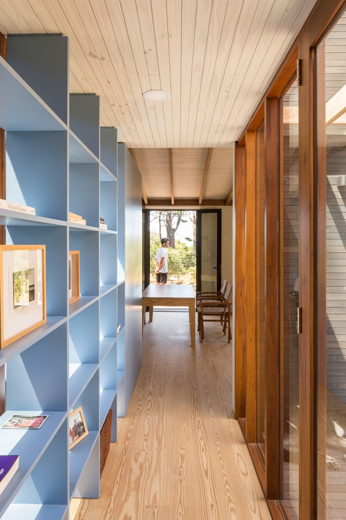 A blue bookshelf is a storage unit and a space divider at the same time