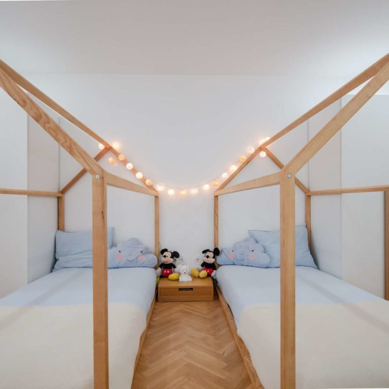 The kids' room is done with two house-shaped beds, lights and touches of blue