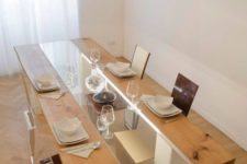 05 a catchy dining table of wood and glass on white geometric legs takes most of the space