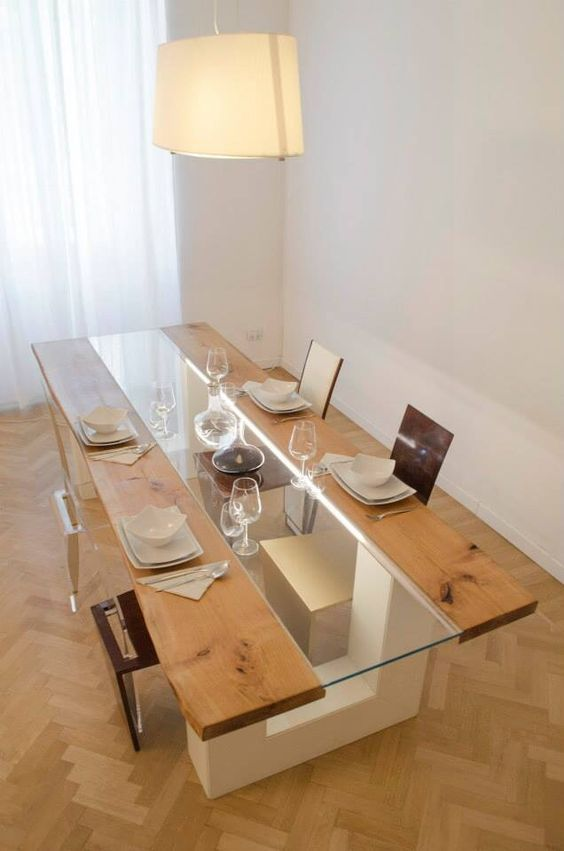 a catchy dining table of wood and glass on white geometric legs takes most of the space