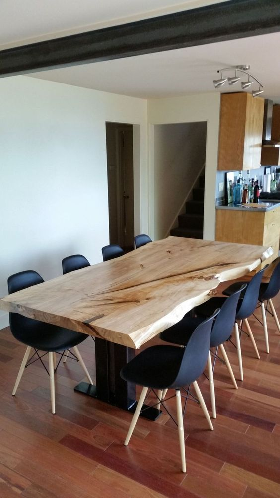 a laconic modern dining space with black chairs and a dining table with a live edge on black legs