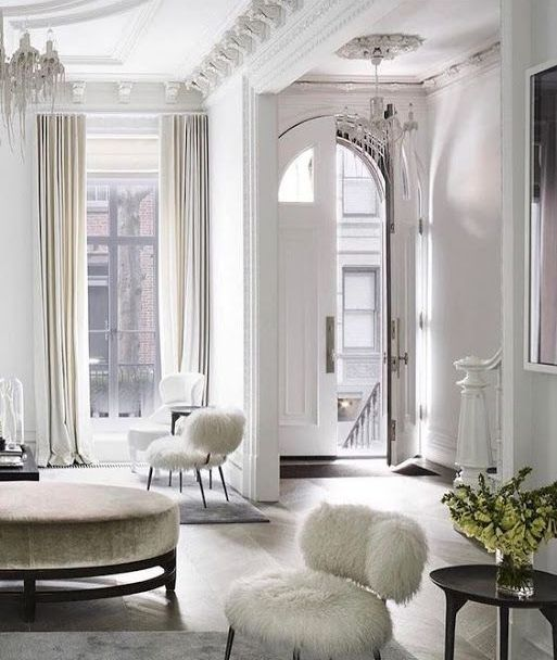 a neutral Parisian living room in white and beige, with high ceilings and large windows is classics