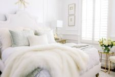 05 a neutral glam bedroom with white walls, a statement crystal chandelier and chic bedding plus faux fur