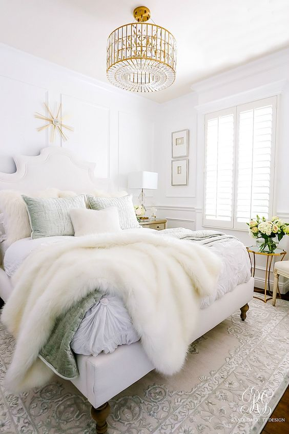 a neutral glam bedroom with white walls, a statement crystal chandelier and chic bedding plus faux fur