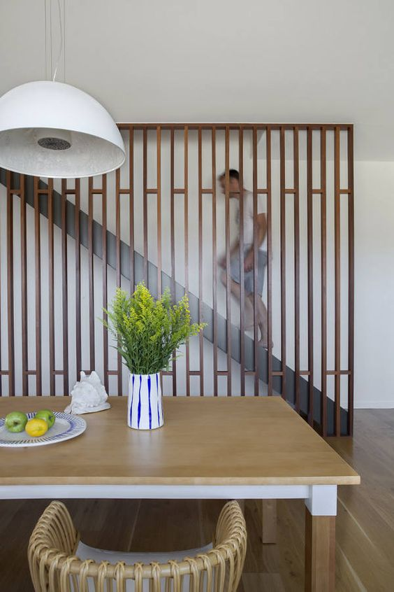 a sleek contemporary wooden screen perfectly finishes the space and separates the staircase from the rest of the home