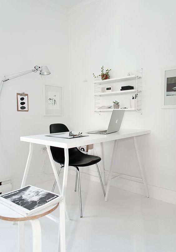 a stylish Nordic home office in white, with a sleek desk, some shelves and negative space