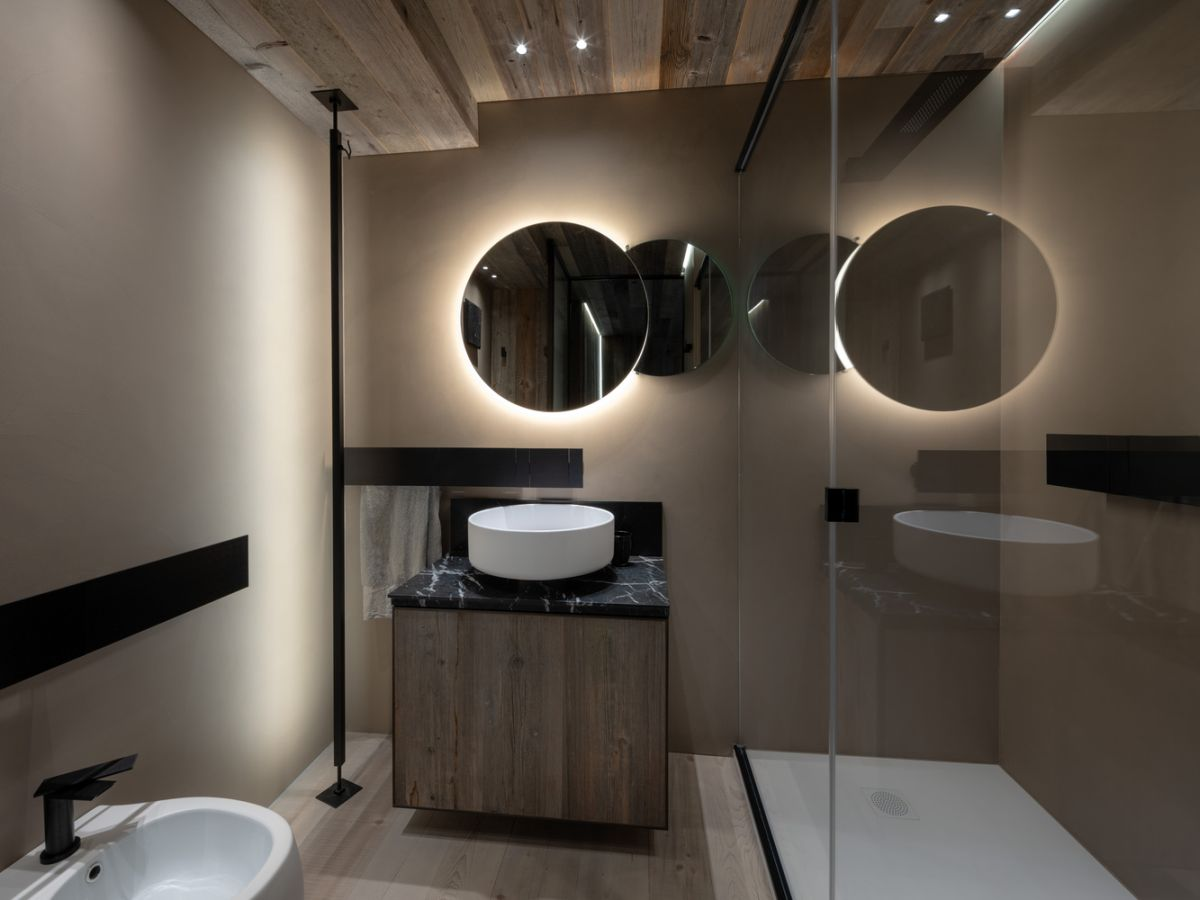 The bathroom also features reclaimed wood, there's a double mirror with lights and minimalist fixtures
