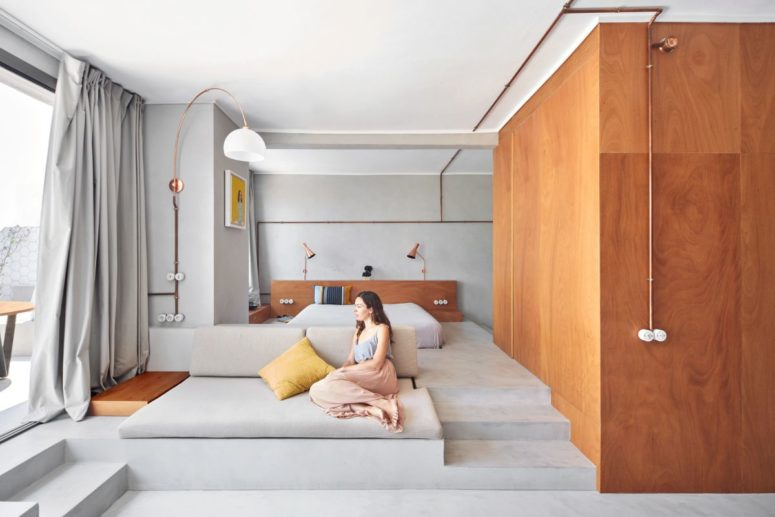 The bedroom features a bed on a platform, lamps and a large window and semalessly flows into a living room that flows into a terrace
