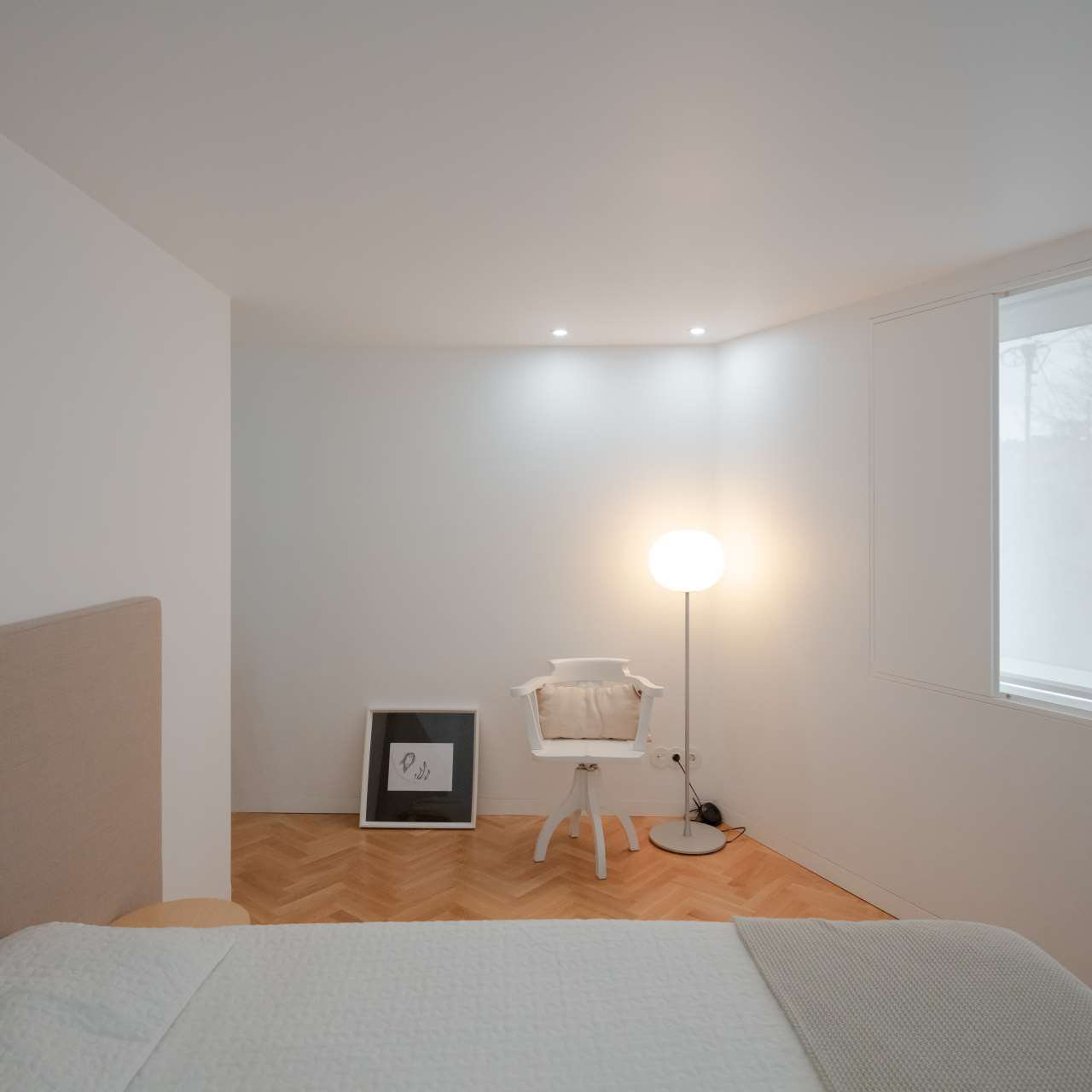 The bedroom is minimalist and neutral, with a floor lamp and a comfy bed