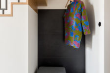 06 The tiny entryway nook is clad with black tiles, an upholstered seat with storage space and a clothes holder