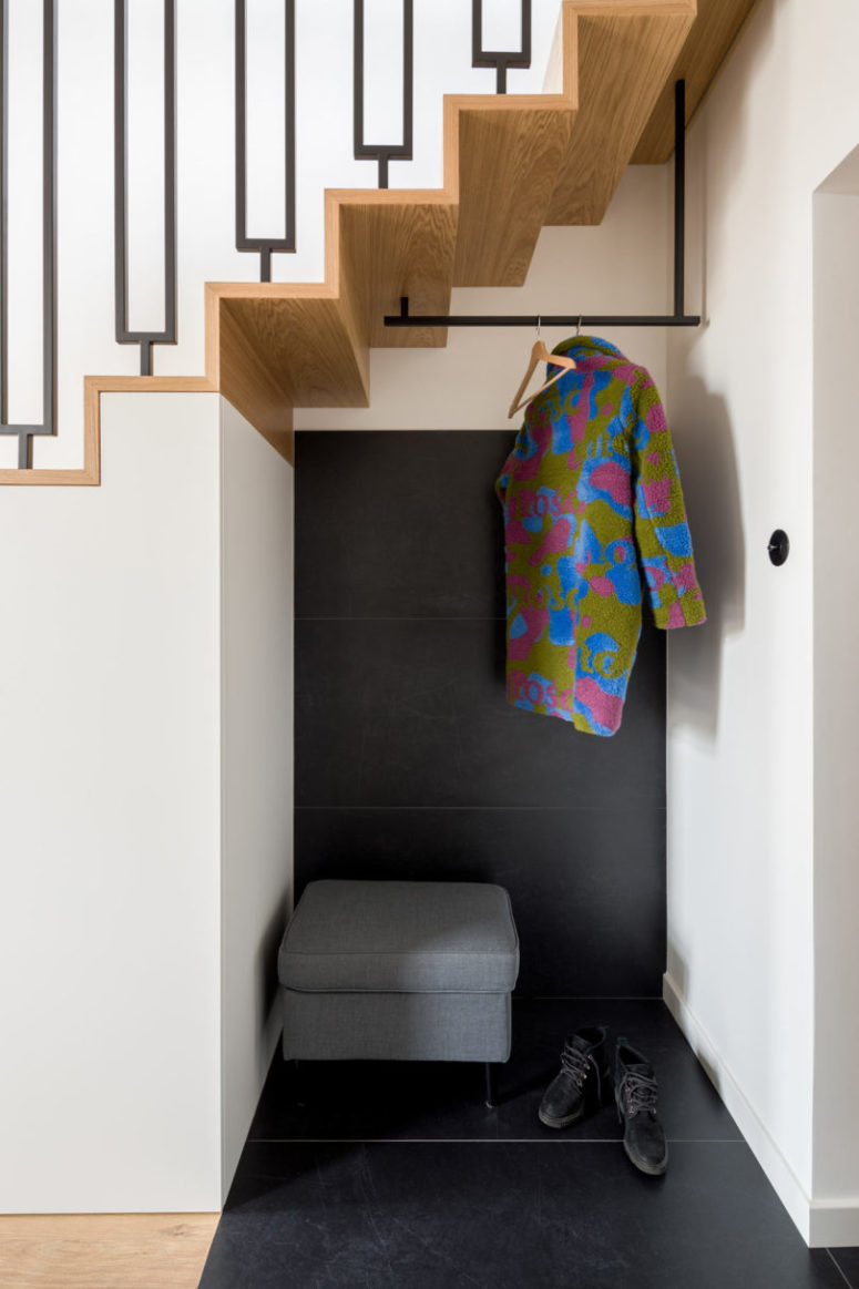 The tiny entryway nook is clad with black tiles, an upholstered seat with storage space and a clothes holder