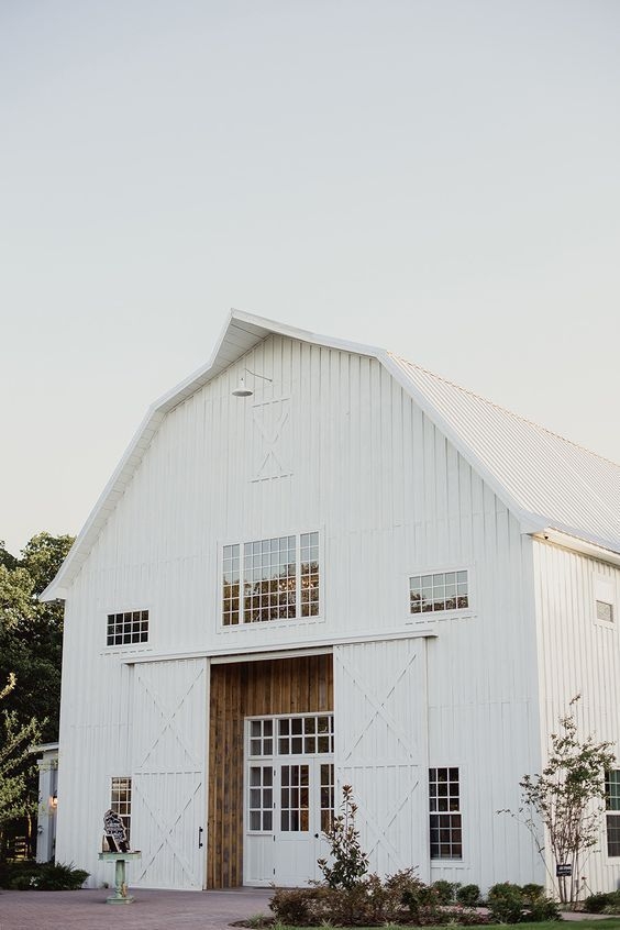 a beautiful white barndominium with stained wood and sliding doors that cover the entrance