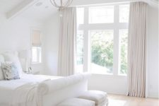06 a very fresh white bedroom with creamy curtains and stools, an elegant chandelier and a white upholstered bed