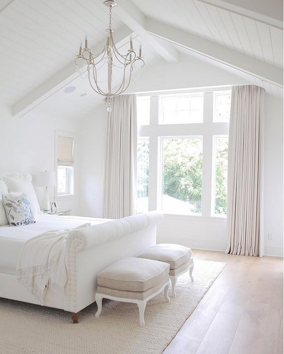 a very fresh white bedroom with creamy curtains and stools, an elegant chandelier and a white upholstered bed